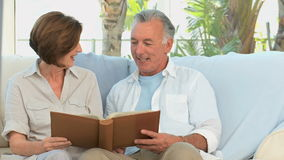 Aged couple looking at a photos album Royalty Free Stock Images