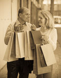 Aged couple with purchases. Smiling senior mature couple staying at street with purchases in hands Royalty Free Stock Image