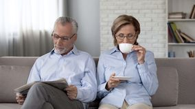 Aged couple sitting on sofa male reading newspaper lady drinking tea, both happy stock photos