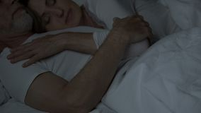 Aged couple sleeping in bed, woman lying on man chest, tender relationship, love