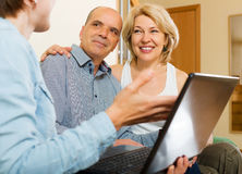 Aged couple talking with employee with laptop Stock Photography