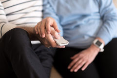 Aged couple watching television together Stock Image