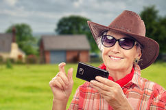 Aged cowgirl surfing internet on smartphone Royalty Free Stock Photo