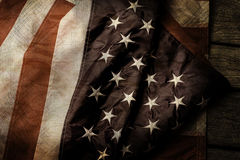 Aged and crumpled US flag. Old flag on wooden background. Courage, honor and loyalty. Fallen shall be forever remembered stock images