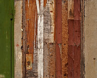Aged damaged door made of various wooden materials Royalty Free Stock Photo