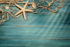 Aged deck with fish net. And seashells Royalty Free Stock Photo