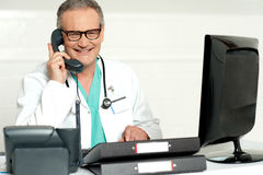 Aged doctor attending call in front of lcd screen. Smiling at camera Royalty Free Stock Photos