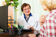 Aged doctor having positive news for a patient Royalty Free Stock Photography