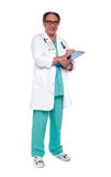 Aged doctor holding clipboard. Full length shot Royalty Free Stock Images