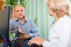 Aged  doctor talking with mature male patient Stock Photo