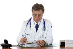 Aged doctor writes down medical report Stock Photo