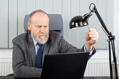 Aged employer at the office. Picture of an aged employer sitting at his desk in the office Stock Photo
