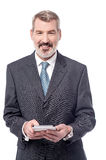 Aged entrepreneur holding tablet pc Stock Image