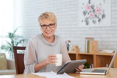 Aged entrepreneur. Portrait of smiling senior female entrepreneur with digital tablet and cup of coffee stock photography