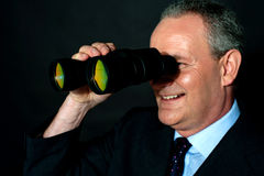 Aged executive monitoring through binoculars Stock Images
