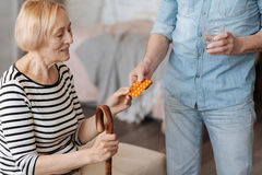 Aged feeble lady having her pill served. For our own sake, honey. Beautiful frail senior women sitting on bed while her husband bringing her the medication and a stock photos