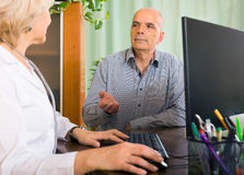 Aged female  doctor talking with mature male patient Stock Image