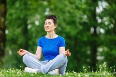 Aged female doing yoga exercise in park. Senior woman practicing yoga outdor. Heathy life style concept. Copyspace. Royalty Free Stock Photography