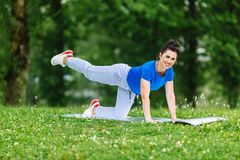Aged female doing yoga exercise in park. Senior woman practicing yoga outdor. Heathy life style concept. Copyspace. Aged female doing yoga exercise in park Stock Photos