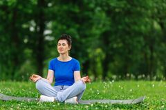 Aged female doing yoga exercise in park. Senior woman practicing yoga outdor. Heathy life style concept. Copyspace. Royalty Free Stock Image