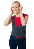 Aged female enjoying music on her music player. Dressed in trendy casuals Stock Photo