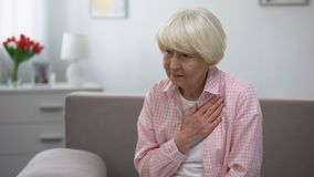 Aged female holding hand on chest, suffering from heart pain, health problems stock video footage