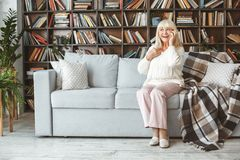 Senior woman at home retirement concept sitting phone call cheerful. Aged female at home in the living room sitting on the coach answering phone cheerful royalty free stock images