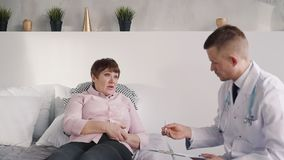 Aged female patient is horizontal lying and talking about her illness and soreness. Professional male doctor is listening, checking information with scans and stock video