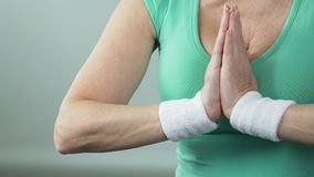 Aged female putting palms one against another in yoga lotus position, hobby. Stock footage stock video