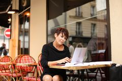 Aged female screenwriter working with scenario in laptop. Aged female screenwriter sitting in outdoor cafe and reproduce scenario from paper drafts in text file Stock Images
