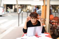Aged female screenwriter working with scenario in laptop. Aged female screenwriter sitting in outdoor cafe and reproduce scenario from paper drafts in text file Stock Photography