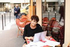Aged female screenwriter working with scenario in laptop. Aged female screenwriter sitting in outdoor cafe and reproduce scenario from paper drafts in text file Stock Photos