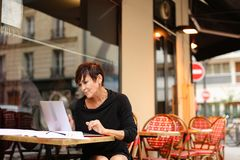 Aged female screenwriter working with scenario in laptop. Aged female screenwriter sitting in outdoor cafe and reproduce scenario from paper drafts in text file Stock Photo