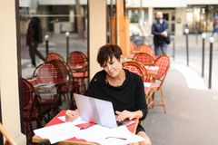 Aged female screenwriter working with scenario in laptop. Aged female screenwriter sitting in outdoor cafe and reproduce scenario from paper drafts in text file Royalty Free Stock Photos