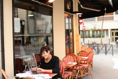 Aged female screenwriter working with scenario in laptop. Aged female screenwriter sitting in outdoor cafe and reproduce scenario from paper drafts in text file Royalty Free Stock Photo