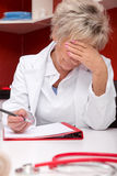 Aged femlae doctor is stressed Royalty Free Stock Photos