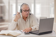 Aged freelance male tutor working online stock images