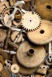 Aged gears cogwheels background. Retro mechanical clock accessories close-up. Shallow depth of field, soft focus. Stock Photos