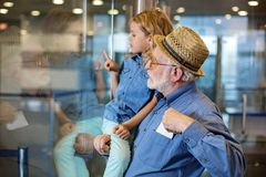 Aged gentleman with child are waiting for flight at airport. Side view profile of concentrated grandfather is standing at terminal hall with his grandoughter on Stock Photography