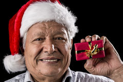 Aged Gentleman with Red Cap Holding Small Gift. Venerable, smiling man wearing a Santa Claus cap is holding up a small red, wrapped Christmas present in his left Stock Photo