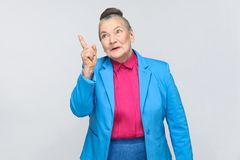 Aged woman have idea. Aged grandma with new idea. Emotion and feelings of handsome expressive grandmother with light blue suit and pink shirt standing with Stock Photos