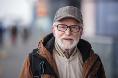 Aged gray-haired male is expressing gladness. Old generation. Portrait of positive senior bearded man with glasses is standing outdoors and looking at camera stock photos