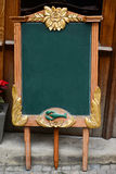 Aged green blackboard in front of restaurant entrance ready for Royalty Free Stock Image