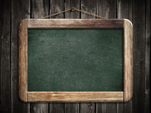 Aged green blackboard hanging on wooden wall Stock Photo