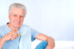 Aged guy brushes teeth Stock Photos