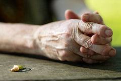Aged hands of an old person on a table Royalty Free Stock Photography