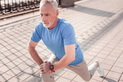 Aged handsome man stretching legs relying on the knee. I will do this. Aged handsome confident man warming up on the street stretching legs relying on the knee royalty free stock photo