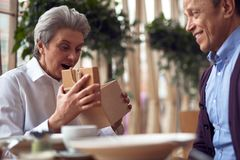 Aged happy surprised woman opening present box. Enjoyable meetings. Close up portrait of happy surprised aged elegant lady opening present box from male friend stock photo
