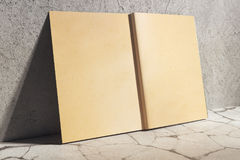 Aged hardcover diary side. Side view of open aged hardcover diary leaning on concrete wall. Abstract supplies, stationery items. Mock up, 3D Rendering Royalty Free Stock Photo