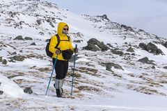 Aged woman is engaged in trekking in winter highlands. Aged hiker woman in bright sportswear is engaged in trekking in winter highlands Royalty Free Stock Photography